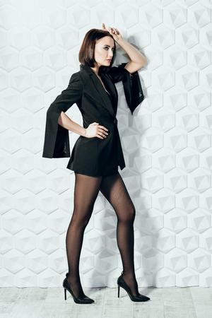 A full length portrait of a beautiful sexy woman wearing a black blazer. Fashion, style, beauty.