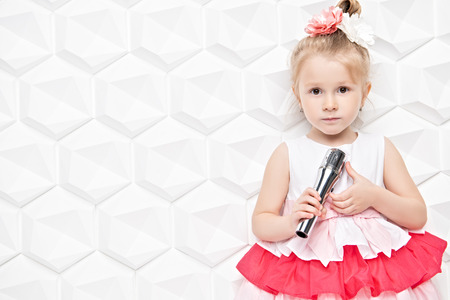 A portrait of a pretty child girl posing in the studio over the background with a microphone. Kids, summer, beauty, talents. Imagens