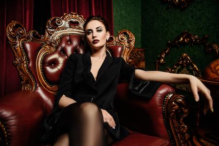 Ein Porträt einer schönen Frau, die einen schwarzen Blazer trägt und im klassischen Interieur auf dem Sessel posiert. Mode, Stil, Schönheit, Interieur. Standard-Bild