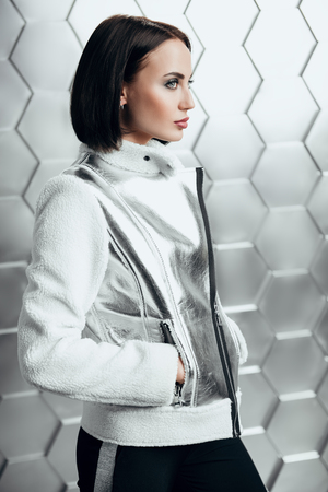 A portrait of a beautiful woman wearing a white and silver coat. Fashion, style. Imagens