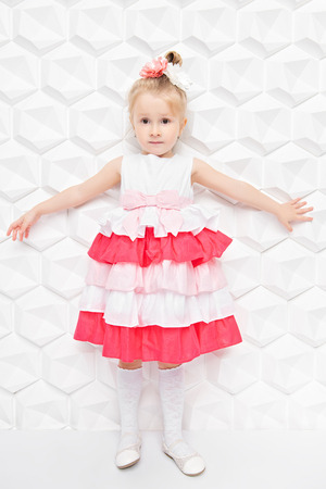 A full length portrait of a pretty child girl posing in the studio over the white background. Kids, summer, beauty.
