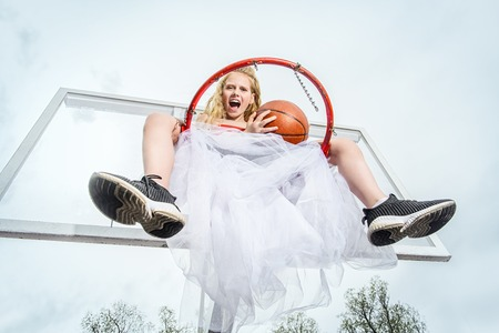 A full length portrait of a sporty teenager girl posing on the basketball pinch in a white fluffy skirt. Sport fashion, active lifestyle, basketball.