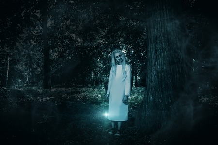 A full length portrait of a scary pale girl from a horror film in the forest. Zombie, halloween. 스톡 콘텐츠