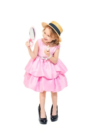 A full length portrait of a pretty girl in a pink dress and high-heeled shoes posing in the studio over the white background and doing make-up. Kids, fashion, beauty. Banco de Imagens