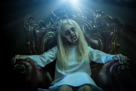 A portrait of a scary pale girl from horror film in the armchair. Zombie, halloween.