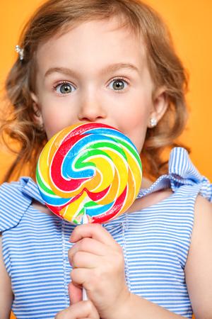 Ein Porträt eines hübschen Mädchens mit einem Lutscher im Studio über dem gelben Hintergrund. Kinder, Schönheit, Essen, Süßigkeiten. Standard-Bild