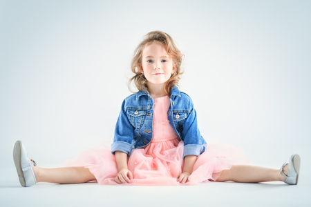 A portrait of a pretty girl in a pink dress and a denim jacket posing in the studio over the white background. Kids, fashion, beauty. Stockfoto