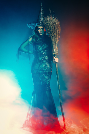 A beautiful lady in a costume of witch holding a broom. Halloween. Celebration. Stock Photo