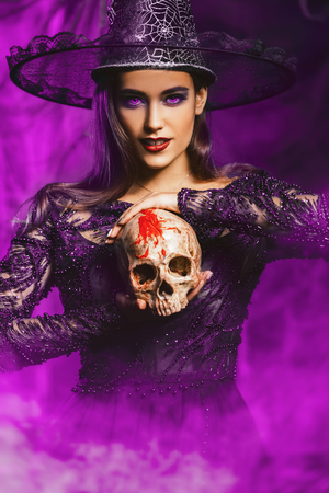 A beautiful lady in a costume of witch with a skull. Halloween. Celebration.