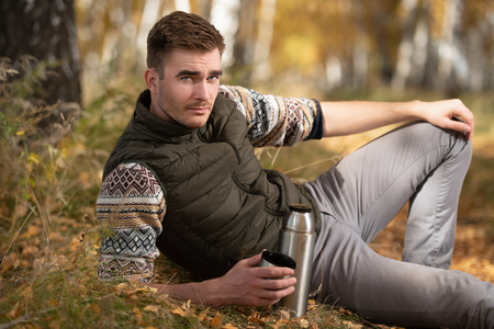 A portrait of a man drinking tea from a thermos in the countryside. Goods for travelling. Active lifestyle, autum fashion.