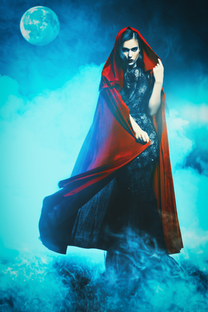 A beautiful lady in a red cloak. Halloween. Celebration. Reklamní fotografie