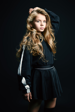 A portrait of a cute emotional girl posing over the black background in studio. Beauty, fashion for kids and teenagers.