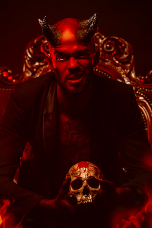 A portrait of a bad demon in his throne with a skull. Horror movie, nightmare. Halloween. 스톡 콘텐츠