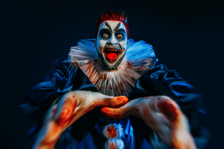 A portrait of an angry crazy clown from a horror film. Halloween, carnival. Фото со стока