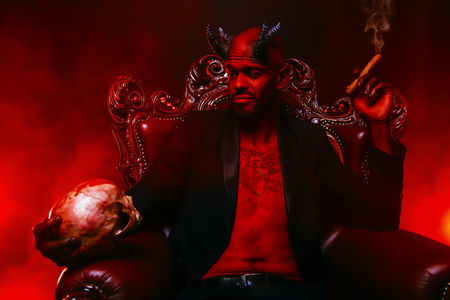 A portrait of a bad demon in his throne with a skull and cigar. Horror movie, nightmare. Halloween.