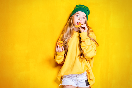 A portrait of a cute girl with flowers over the yellow background. Beauty, fashion for kids and teenagers. Stock Photo