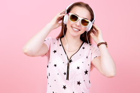 A portrait of a bright beautiful girl in the studio over the yellow background. Summer casual fashion, beauty, optics, music.
