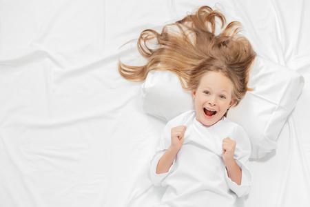 A portrait of a young pretty laughing girl in bed. Relax, pajamas. Banco de Imagens