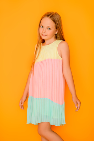 A portrait of a shy young pretty girl. Kids summer casual fashion, beauty, emotions.