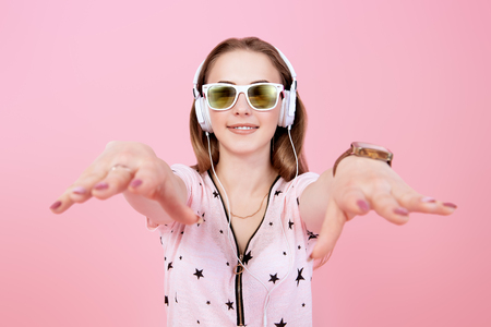 A portrait of a bright beautiful girl in the studio over the yellow background. Summer casual fashion, beauty, optics, music. Stock Photo - 128638127
