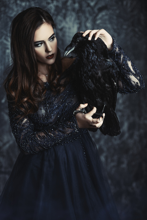 A witch in a dress with a raven. Halloween. Celebration.