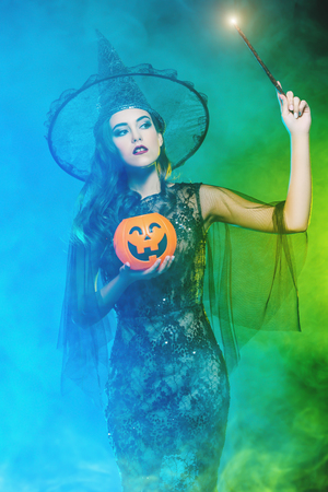 A beautiful witch in a hat holding a magic stick and a pumpkin. Halloween. Celebration. Stock Photo
