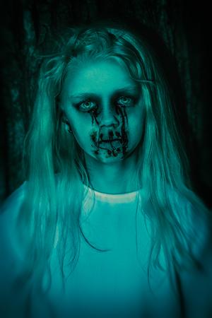 Un retrato de una aterradora niña pálida de una película de terror en el bosque. Zombie, halloween.