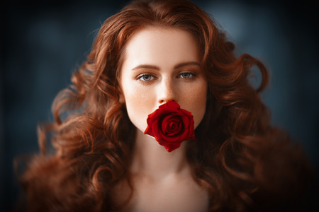 A close-up portrait of a lovely mysterious girl with a red rose. Beauty, cosmetics.
