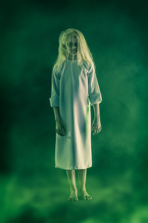 A full length portrait of a scary pale girl from a horror film. Zombie, halloween.