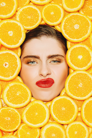 A portrait of a bright beautiful girl with juicy oranges posing in the studio over the yellow background. Beauty, health. 写真素材