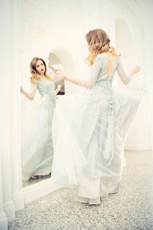 Un ritratto di una bella donna elegante nell'abito da sposa svolazzante. Moda, abito da sposa.