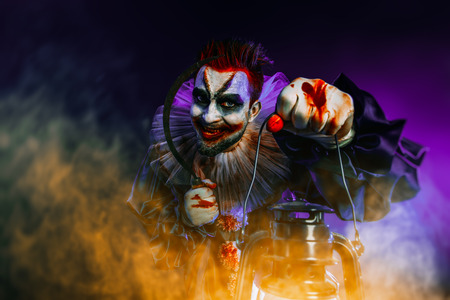 A portrait of an angry crazy clown from a horror film with a lantern. Halloween, carnival. Stok Fotoğraf