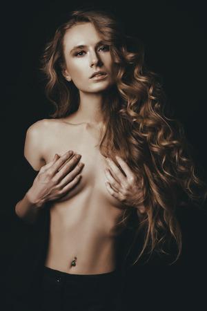 Ritratto di una ragazza con lunghi capelli ricci su sfondo nero. Bellezza, moda. Archivio Fotografico