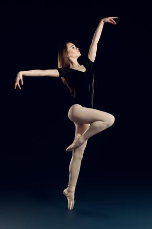 A full length portrait of an elegant refined ballet female dancer posing in the studio over the black background. Talent, fashion for ballet dancers.