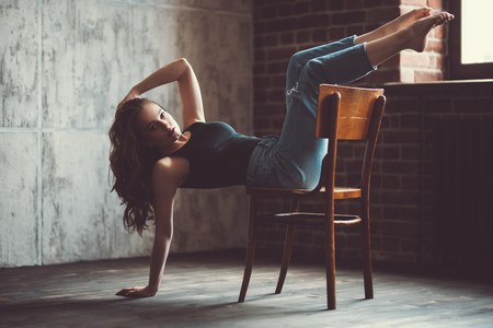 A portrait of a young beautiful woman posing on the chair in the room. Casual fashion, beauty. Standard-Bild - 129016198