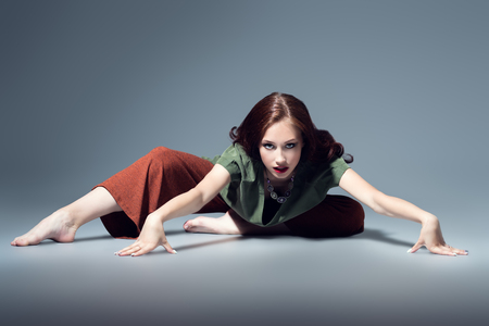 Un portrait en pied d'une belle jeune femme dansant sur fond gris en studio. Mode décontractée, fitness, yoga. Banque d'images