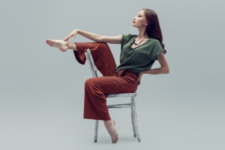 A full length portrait of a beautiful young woman with the chair over the grey background in the studio. Casual fashion. Standard-Bild - 129011624