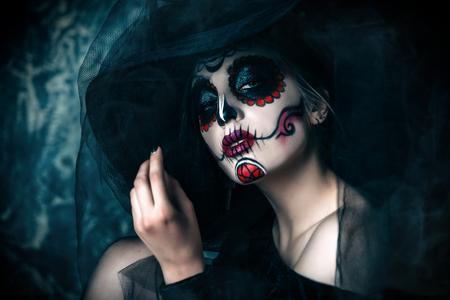 Retrato de una hermosa y aterradora Calavera Catrina en vestido negro y sombrero negro con velo sobre fondo oscuro. Maquillaje de calavera de azúcar. Dia de los muertos. Dia de los Muertos. Víspera de Todos los Santos.