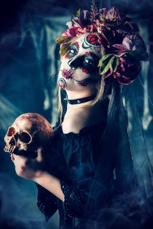Calavera Catrina in black dress holding a skull over dark scary background. Sugar skull makeup. Dia de los muertos. Day of The Dead. Halloween. Stock Photo