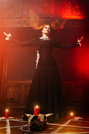 A full length portrait of a scary witch in the wooden house. Magic, dark force, spell. Stock Photo