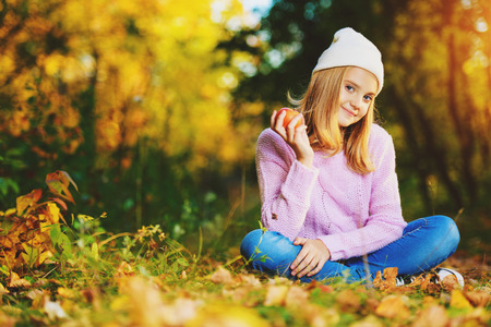 A pretty young girl is sitting on the ground with golden leaves and holding an apple. Autumn fashion, beauty. Healthy lifestyle.