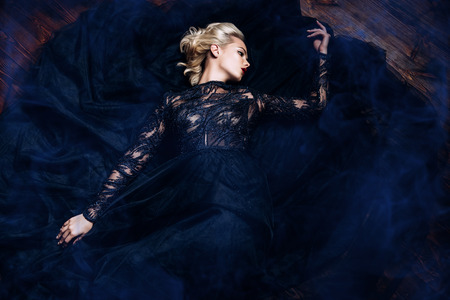 A beautiful blonde lady is lying on the floor. Evening dress. Fashion, beauty.