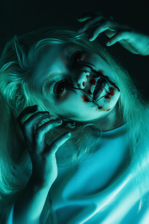 A close up portrait of a scary pale girl from horror film. Zombie, halloween. Banco de Imagens