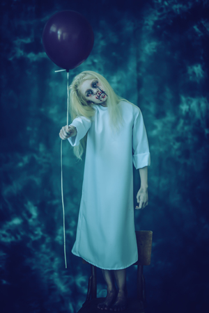 A full length portrait of a scary pale girl from a horror film in the forest with a baloon on the chair. Zombie, halloween. Banco de Imagens