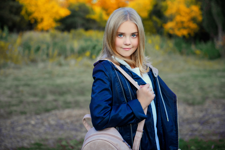A beautiful young girl with a backpack in the coutryside. Autumn fashion, beauty. Imagens