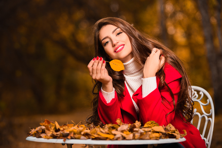 A portrait of a beautiful young woman sitting at a table covered with golden autumn leaves. Lifestyle, autumn fashion, beauty.