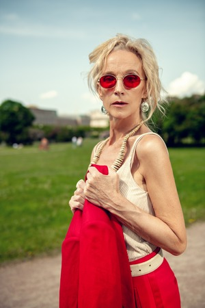 A portrait of an elderly stylish woman in the summer park. Beauty, fashion, optics. Archivio Fotografico - 130500706
