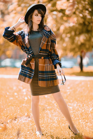 A full length portrait of a young fashionable woman in the park. Beauty, fashion.