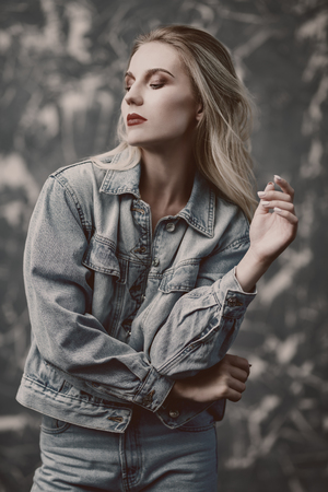 A portrait of a romantic young lady posing in the studio. Cosmetics, makeup, beauty, denim casual fashion.