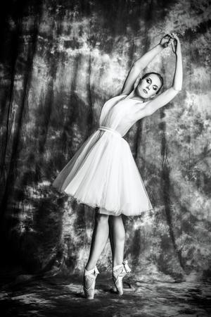 A full length monochrome portrait of an elegant female ballet dancer posing in the studio over the grunge background. Talent, fashion for ballet dancers.